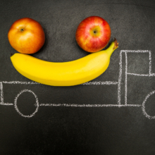 Two bananas and an apple in the back of a chalk truck.